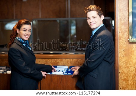 Casual shot of young help desk executives checking customer records while posing in front of camera