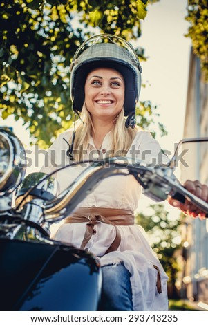 Casual smiling blond woman in moto helmet posing on scooter on nature background.