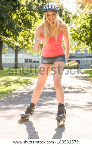 Casual smiling blonde inline skating in a park - stock photo