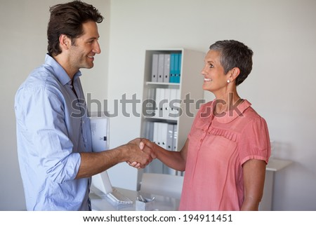 Casual smiling business people shaking hands in the office