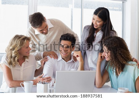Casual smiling business team congratulating their colleague in the office - stock photo