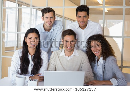 Casual smiling business team having a meeting using laptop in the office