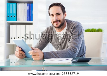 Casual smiling businessman using tablet and calculator in the office - stock photo