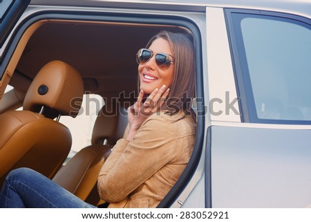 Casual smiling girl in sunglasses in a car's back seat. - stock photo