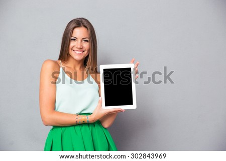 Casual smiling woman showing blank tablet computer screen over gray background. Looking at camera - stock photo