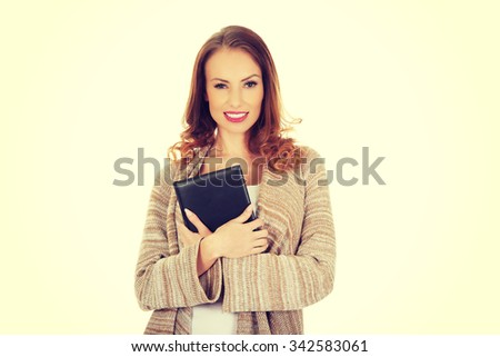 Casual smiling woman with a notebook.