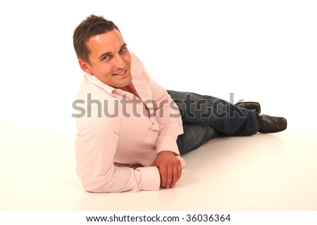 Casual smiling young man reclining on the ground