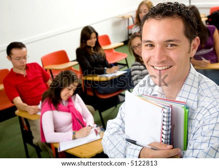 casual student or teacher in a classroom full of students - stock photo