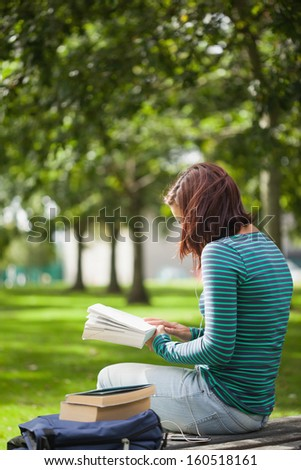 Casual student sitting on bench reading on campus at college - stock photo