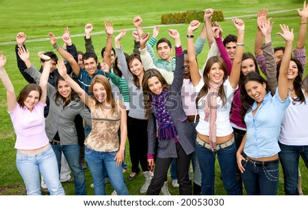 casual students smiling and celebrating success in a park - stock photo