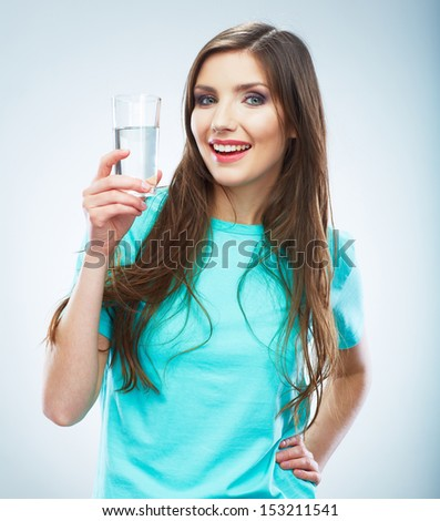 Casual style young woman posing on isolated studio background, hold water glass. Beautiful girl portrait. Female model poses.