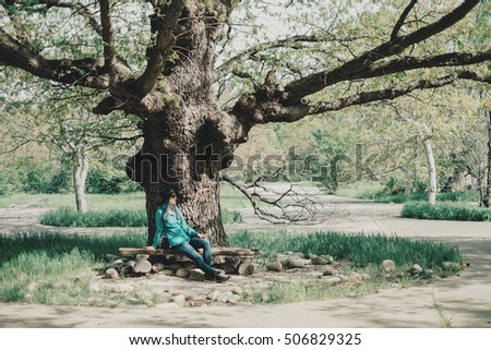 Casual style young woman resting on bench near the oak tree in spring