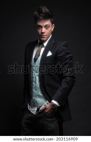 Casual stylish young business man wearing dark blue striped jacket with tie and gilet. Studio shot against black.