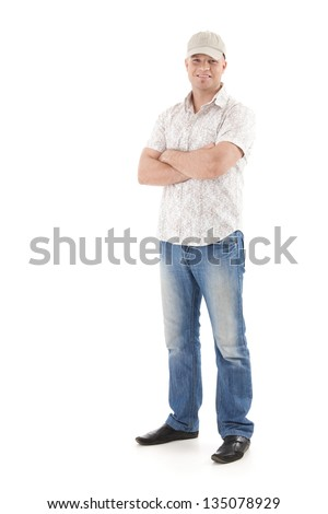 Casual summer portrait of young man wearing baseball hat, smiling, standing with arms folded, isolated on white. - stock photo