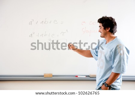 casual teacher or student writing on a whiteboard - stock photo