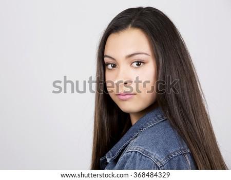 casual teen girl posing on light grey background - stock photo