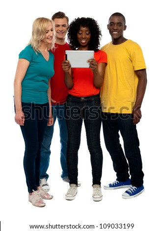 Casual teen group watching video on tablet pc, full length shot - stock photo