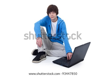 Casual teenager boy sitting on the floor with a laptop computer - isolated - stock photo