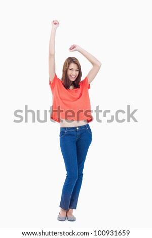 Casual teenager smiling and raising her arms above her head - stock photo