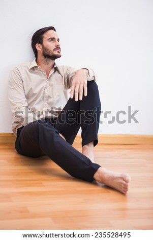 Casual thoughtful man leaning against wall looking up in the living room