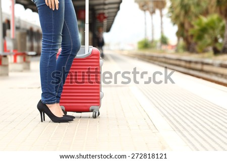 Casual traveler tourist legs waiting in a train station with a suitcase  - stock photo