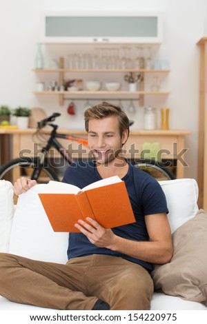 Casual unshaven handsome young man relaxing at home on a sofa in the living room reading a book or studying - stock photo