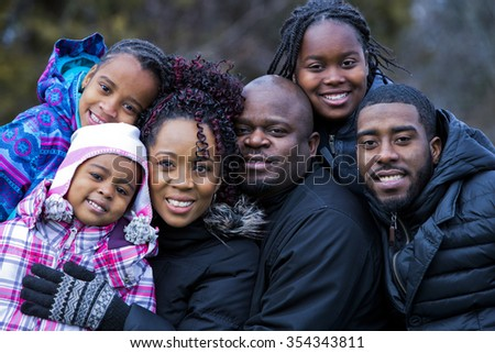casual winter young black family outdoors in the park - stock photo