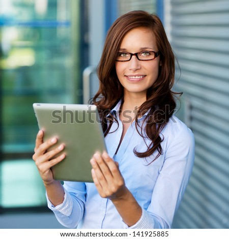 Casual woman browsing the internet through her tablet outdoors - stock photo