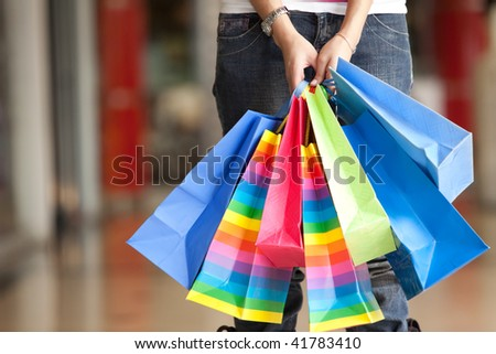 Casual woman carrying shopping bags in a mall - stock photo
