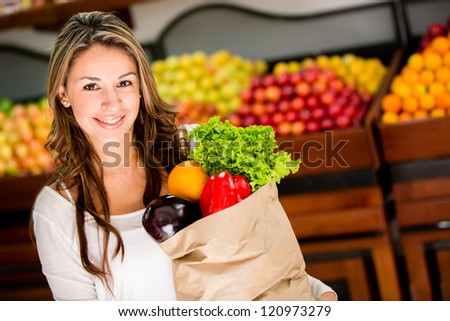 Casual woman grocery shopping and looking happy - stock photo