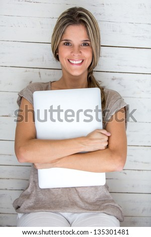 Casual woman holding a laptop computer and smiling - stock photo