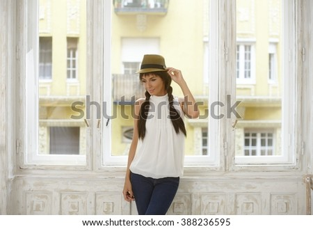 Casual woman in hat with long hair standing at window, looking away, daydreaming. - stock photo