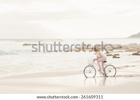 Casual woman on a bike ride at the beach - stock photo