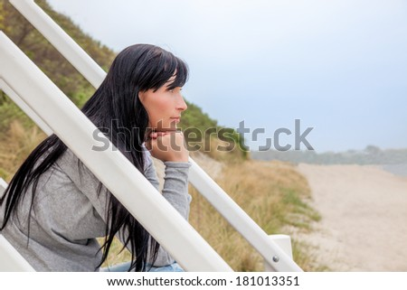 casual woman relaxing on coast  - stock photo