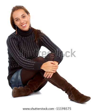 casual woman smiling sitting on the floor isolated over a white background