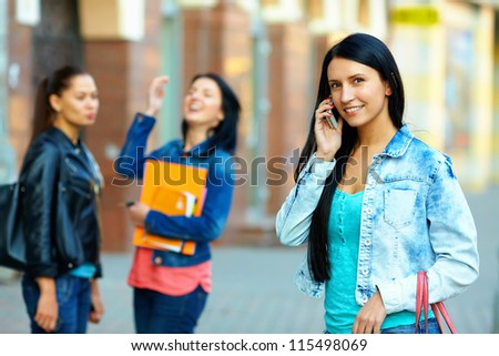 casual woman talking on the mobile phone on the street - stock photo