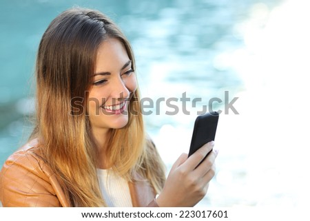 Casual woman using a smart phone with the sea in the background isolated on white in right side