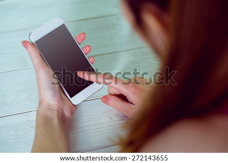 Casual woman using her smartphone at home in the living room - stock photo