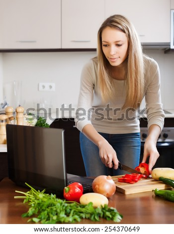 Casual woman using notebook while cooking vegetables at home kitchen
