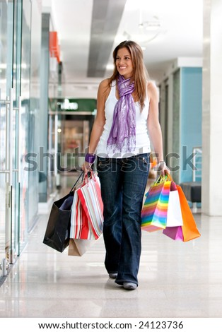 Casual woman walking with shopping bags in a mall - stock photo