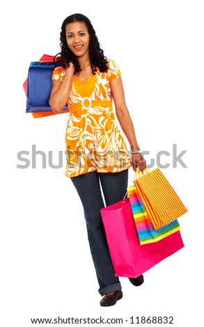 Casual woman walking with shopping bags isolated over a white background - stock photo
