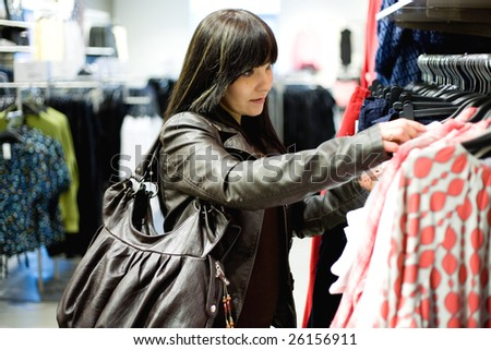 casual woman watching clothes in store - stock photo