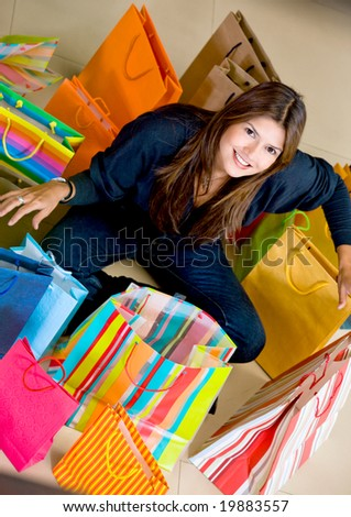 Casual woman with shopping bags in a store smiling - stock photo