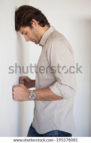 Casual worried businessman leaning on wall in his office - stock photo