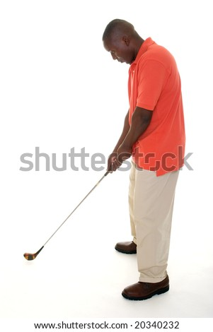 Casual young African American man in a bright orange golf shirt holding a golf club to lining up a drive and preparing to swing. - stock photo