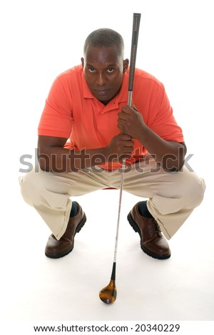 Casual young African American man in a bright orange golf shirt with a golf club lining up a putt. - stock photo