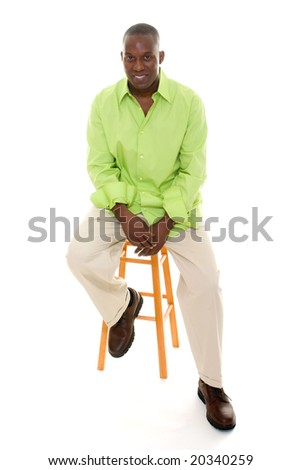 Casual young African American man standing in a bright green shirt sitting comfortably on a stool. - stock photo