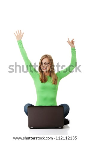 Casual young blond woman working on her laptop computer - stock photo