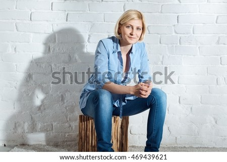 Casual young blonde woman sitting on stool front of white brick wall, smiling, looking at camera.