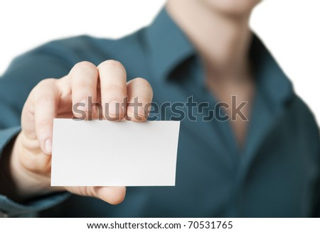 Casual young businessman holding business card. Close up shot focused on the hand holding the card with intentionally shallow depth of field. - stock photo